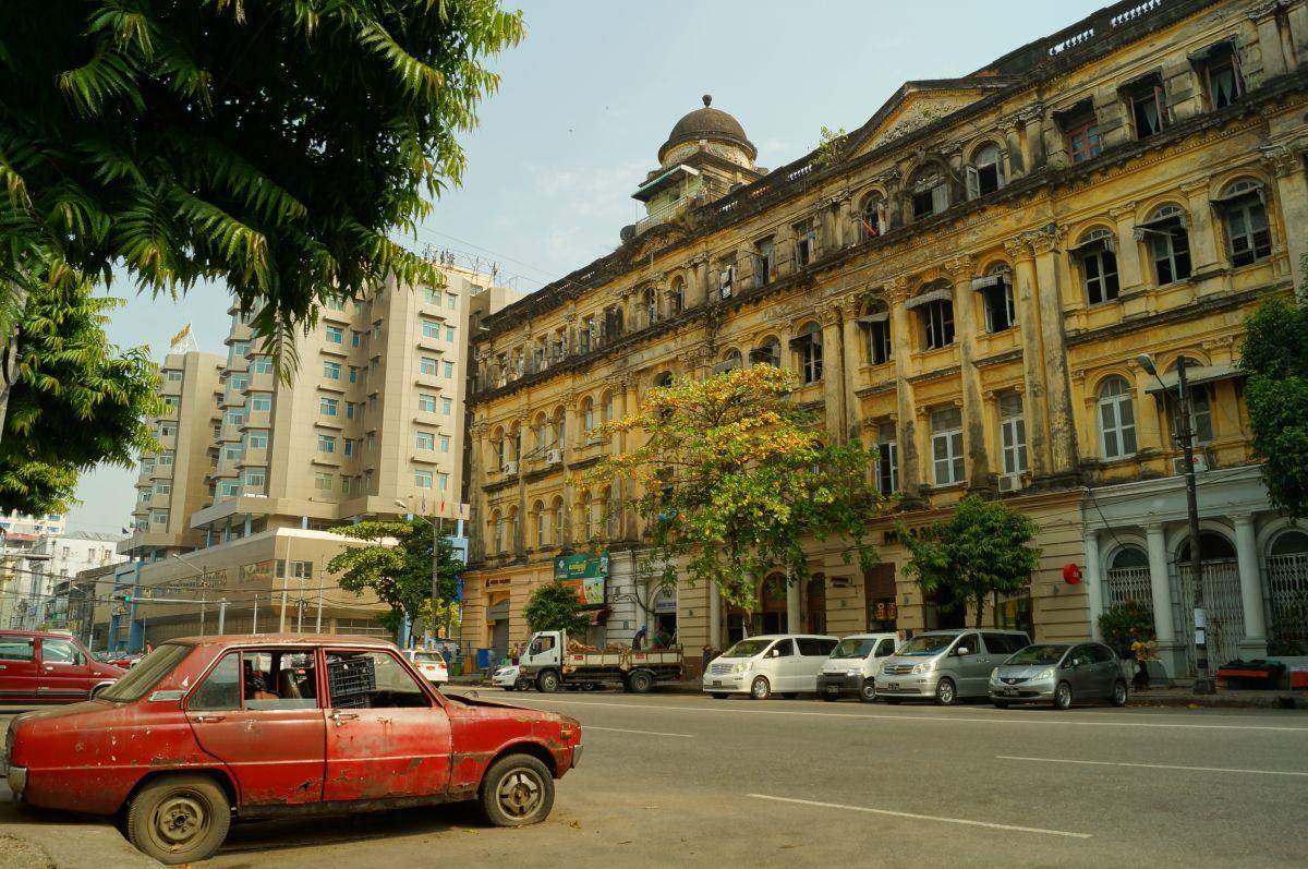 Altes rotes Auto vor verfallenem Gebäude in Yangon Myanmar