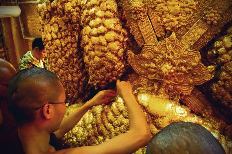 Mönch klebt Blattgold aus Mahamuni Buddha Statue