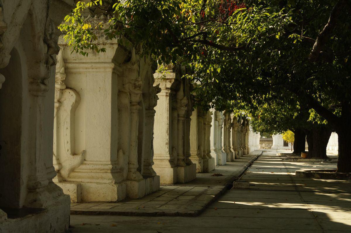 Schatten spendende Bäume und weiße Pagoden in Mandalay