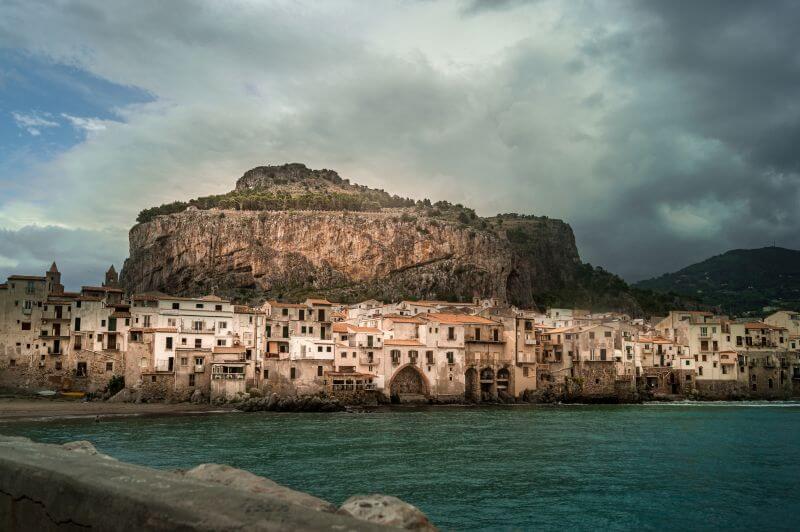 Blick über Cefalù von der Küste aus mit dem Felsen im Hintergrund