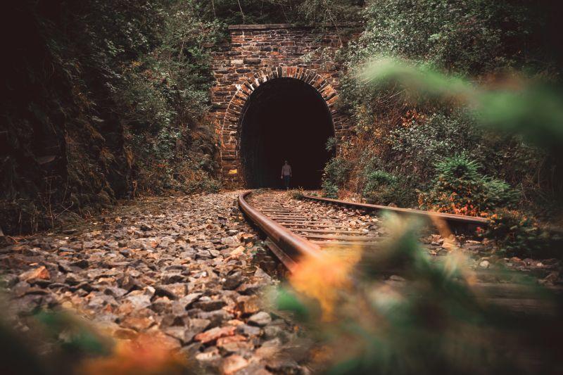 Mann läuft in Tunnel an stillgelegten Gleisen.